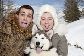 Young couple with a malamute puppy — Stock Photo