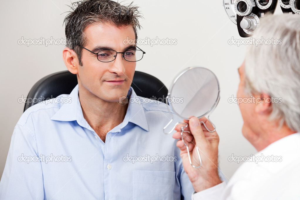 Man in stylish reading glasses while looking at mirror with optometrist in the clinic — Stock Photo #10020959