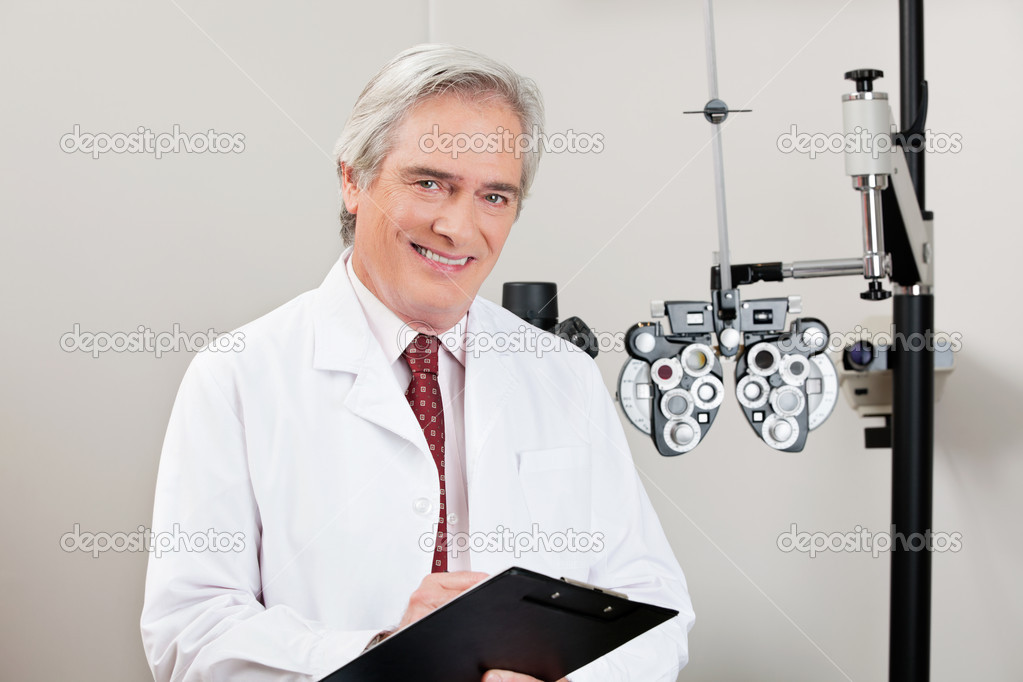 Experienced optometrist smiling with notepad in his clinic — Stock Photo #10022929