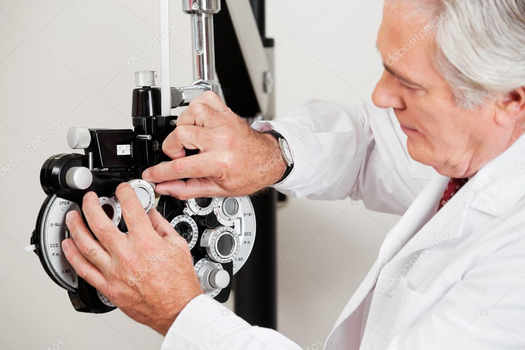 Optometrist changing lens in phoropter for eye examination  Stock Photo #10023257