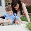 Mother Drawing With Chalk On Sidewalk With Son - Stock Photo