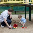 Father And Son Playing At Playground In Sand — Stock Photo