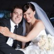 Stock Photo: Happy Wedding Couple in Limo