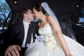 Newlywed Couple In Limousine — Stock Photo