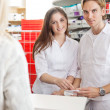 Pharmacists with Customer at the Counter — Stock Photo