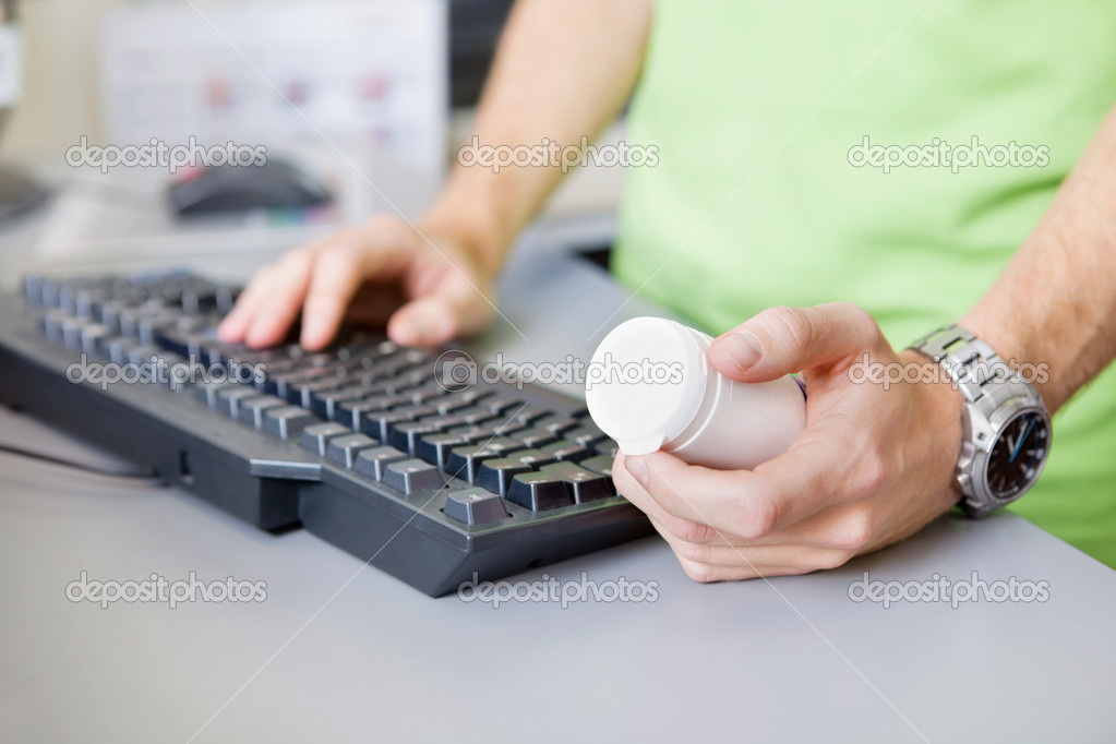 Cropped image of male hand holding medicine container while typing on keyboard — Stock Photo #8811905
