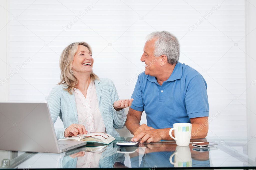Happy couple at dining table working on laptop on house finance — Stock Photo #8812050