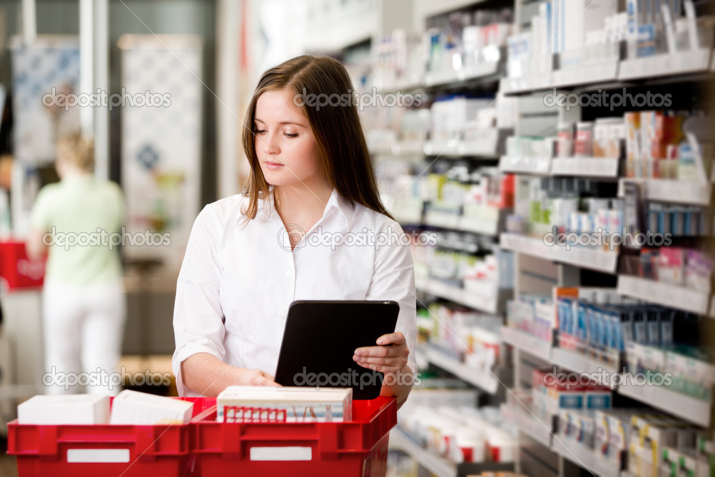 Female pharmacist working in pharmacy with digital tablet and medicine — Stock Photo #8812461