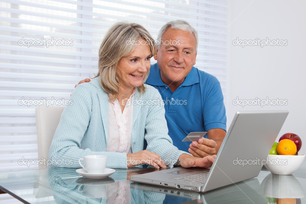 Senior couple shopping online using laptop with credit card  Stock Photo #8825832
