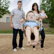 Father And Mother Pushing Boy On Swing - Foto Stock
