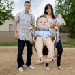 Father And Mother Pushing Boy On Swing — Stock Photo #9185019