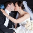 Newlywed Couple Kissing In Limousine — Stock Photo