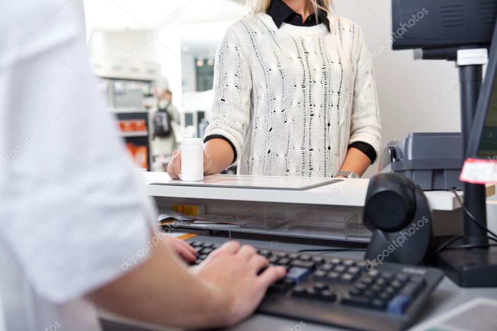 Mid-section of customer standing at checkout counter in drugstore — Stock Photo #9180723