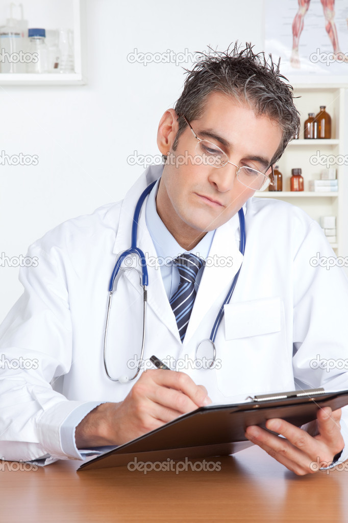 Doctor writing on clipboard sitting at desk. — Stock Photo #9183020