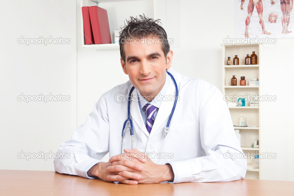 Portrait of male doctor sitting at desk . — Stockfoto #9183678