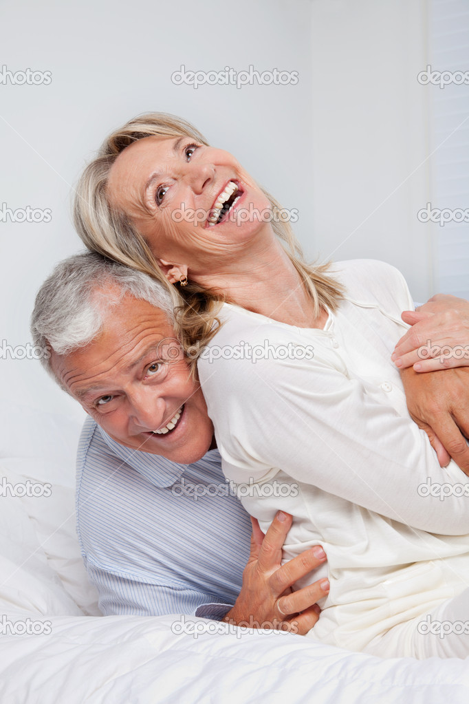 Excited senior couple laughing together on bed — Stock Photo #9184285