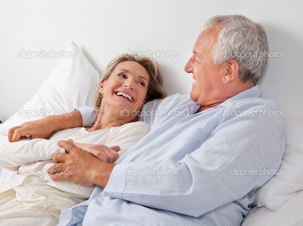 Cheerful couple relaxing on bed at home — Stock Photo #9184314