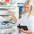 Female Chemist Standing in Pharmacy Drugstore - Stock Photo