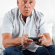 Senior Man Playing Video Game - Stock Photo