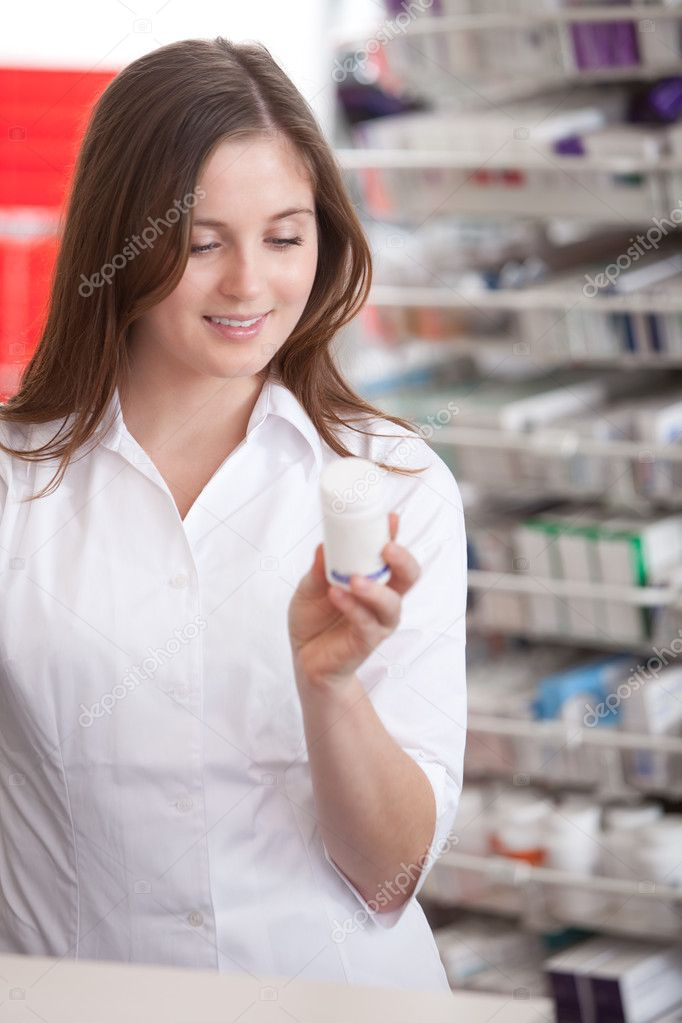 Portrait Of A Female Pharmacist At Pharmacy Reading Information On Medicine. — Stock Photo #9313676