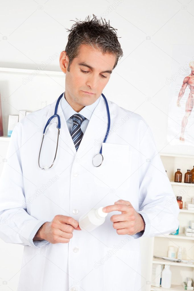 Male doctor holding a bottle of pills.  Stock Photo #9319716