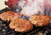 Burger patties on a grill — Stock Photo