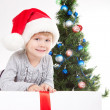 Little girl near the Christmas Tree — Stock Photo #8015328