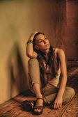 Girl sitting on wooden floor — Stock Photo