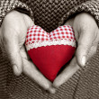 Heart in old hands - Stock Photo