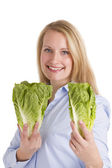 Smiling Blonde Woman Presenting Two Salad Lettuces — Stock Photo