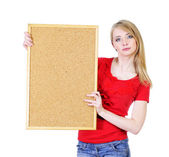 Young blond woman holding a cork board — Stockfoto