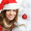 Stock Photo: Smiling woman with gift and Christmas tree - face closeup