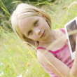 Teen girl reading electronic device - e-book — Stock Photo