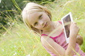 Teen girl reading electronic device - e-book — Stockfoto