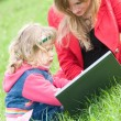 Mom and little daughter with laptop outdoor — Stock Photo