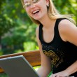 Happy young woman with laptop — Stock Photo