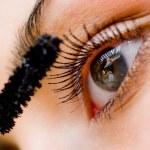 Beautiful woman applying mascara on her eye with brush — Stock Photo #10166273