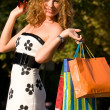 Attractive red-haired woman with shopping bags — Stock Photo