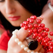 Pretty brunette holding red and white beads in hand — Стоковая фотография