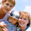 Happy smiling family on blue sky background — Stok fotoğraf #10166511
