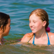 Cute teenager girls playing at sea water — Stock Photo