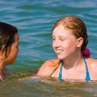 Cute teenager girls playing at sea water — Stock Photo #10166516