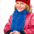 Photo: Pretty joyful little girl dressed winter clothes isolated over w