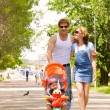 Family with child in stroller walking across city park — Stock Photo