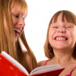 Two little girls looking like sisters holding red book, laughing — Stok Fotoğraf #10166592