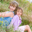 Pretty children and teenager girls on green grass — Stock Photo
