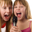 Two cute girls, 9 and 12 years age singing to microphone, isolat — стоковое фото #10166614