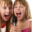Two cute girls, 9 and 12 years age singing to microphone, isolat — Stock Photo