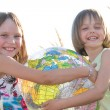 Happy girls holding globe — Stock Photo