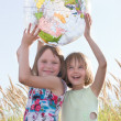 Happy girls holding globe — Stockfoto